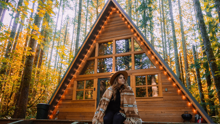 Eine Frau sitzt vor einer Holzhütte im Wald.