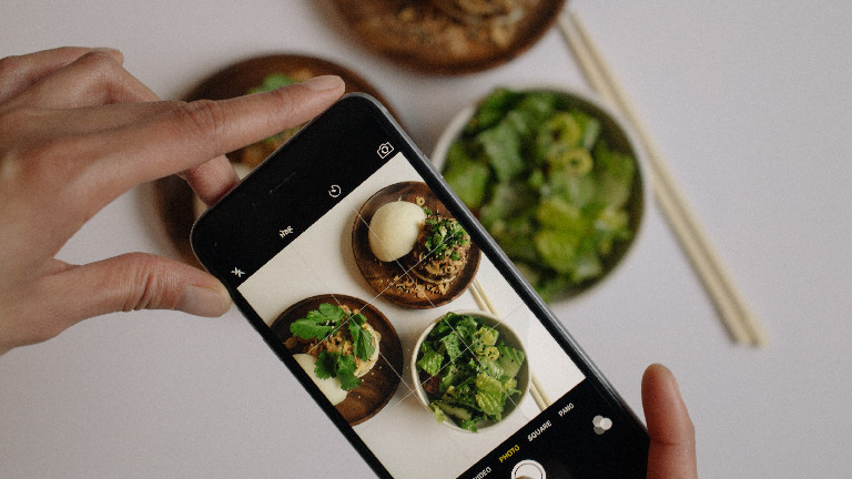 Eine Hand fotografiert Essen.