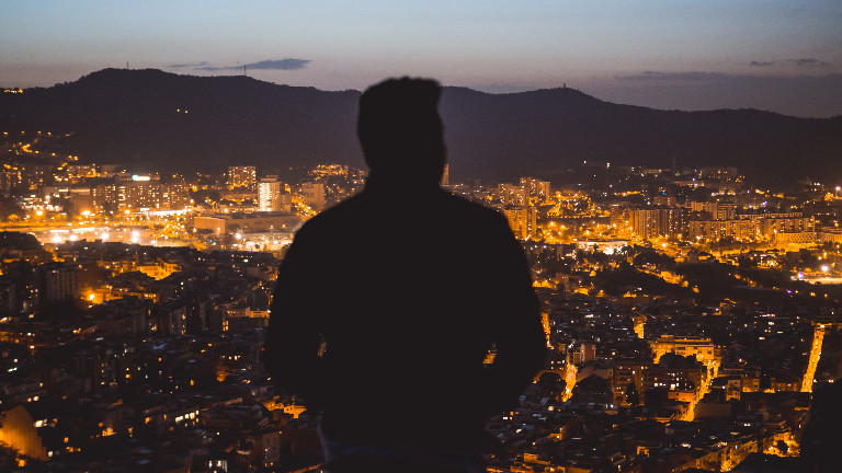 Ein Mann steht vor einer Stadt-Skyline.