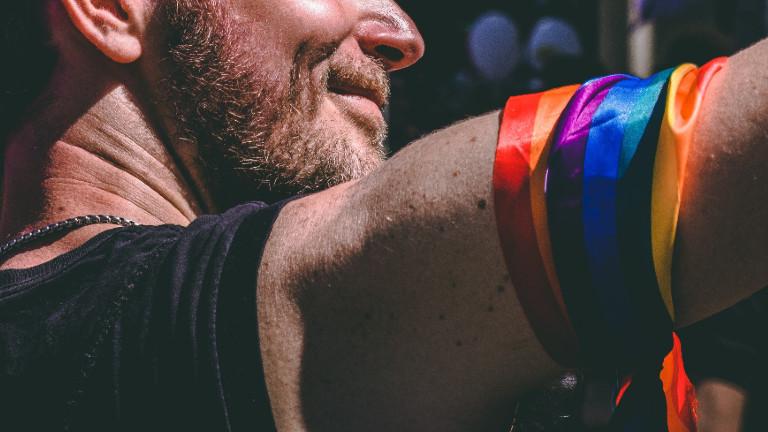 Ein Mann mit Regenbogenfahne um den Arm
