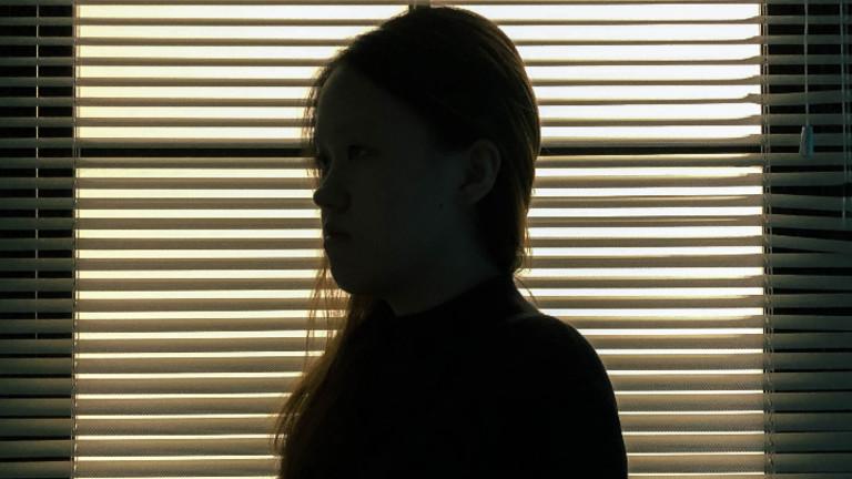 Die Silhouette einer jungen Frau vor einem Fenster.