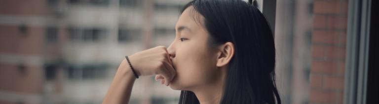 Eine junge Frau schaut aus dem Fenster.