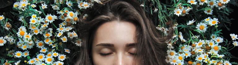 Eine junge Frau liegt mit geschlossenen Augen in einer Blumenwiese.