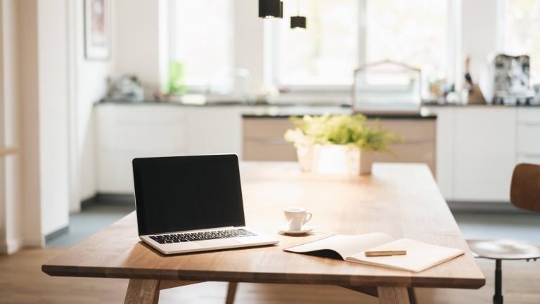 Homeoffice: Laptop und Kaffeetasse auf einem Küchentisch.