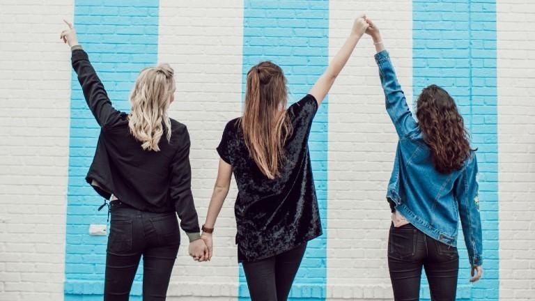 Rückenansicht: drei Freundinnen, die sich an den Händen fassen
