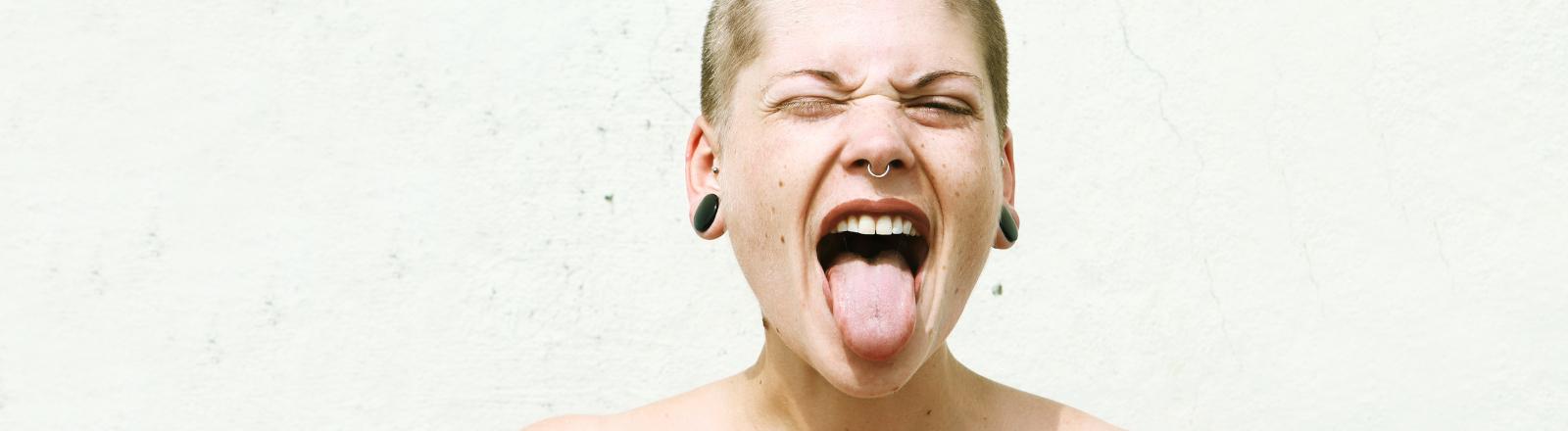 Frau steckt fröhlich ihre Zunge raus