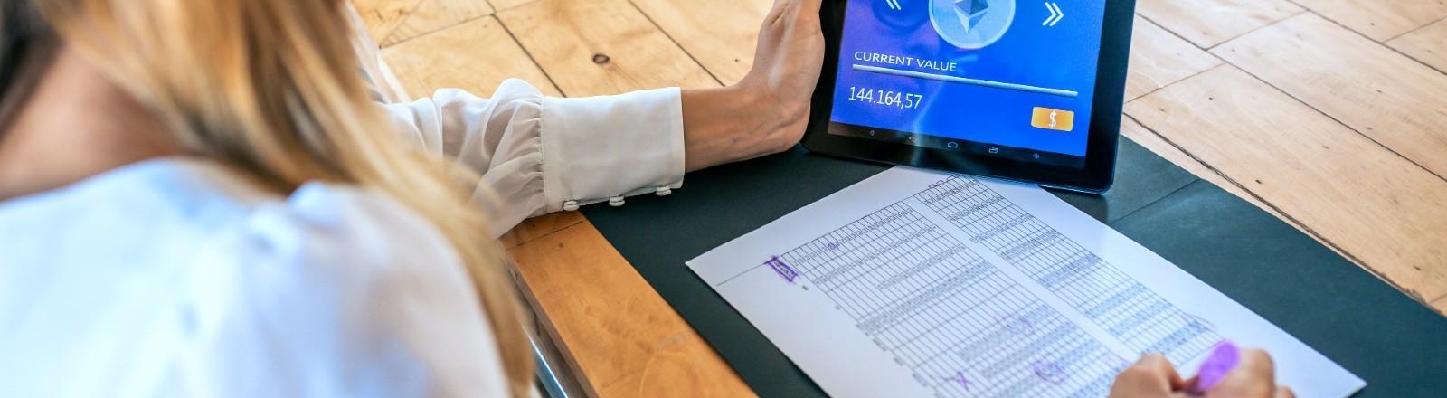 Junge Frau checkt Aktienkurse auf einem Tablet und notiert die Daten in eine Tabelle.