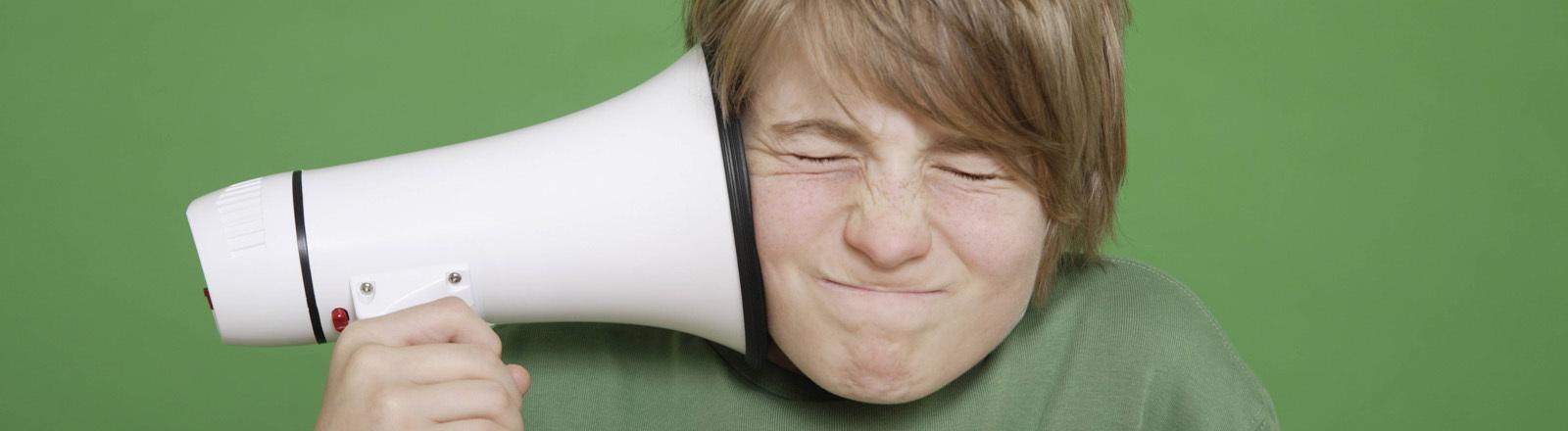 Junge hält sich Megaphon ans Ohr