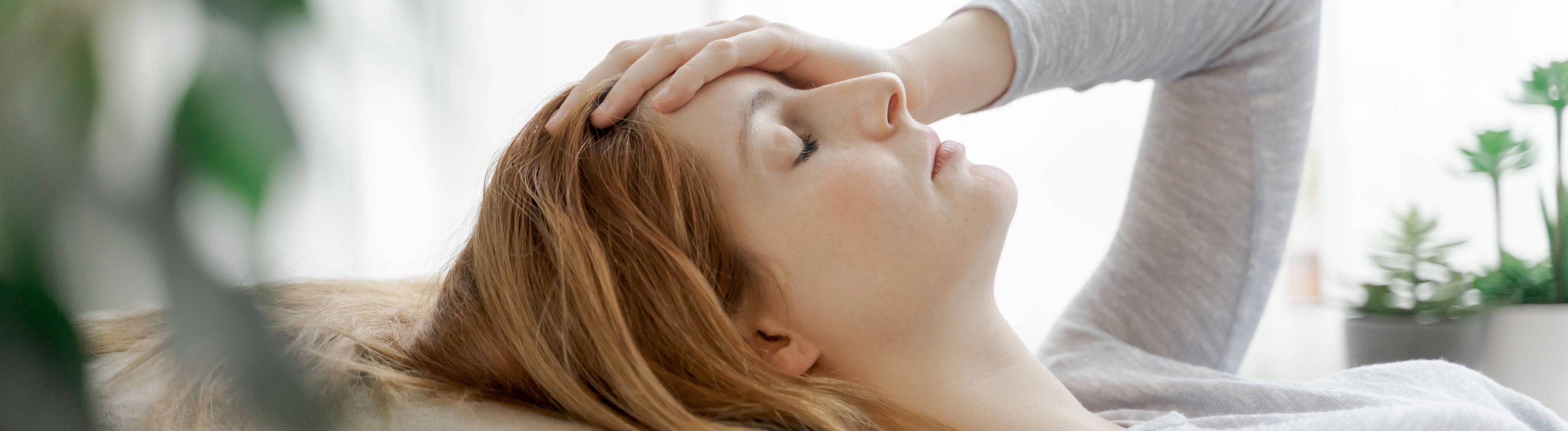 Frau hält sich besorgt die Hand an die Stirn