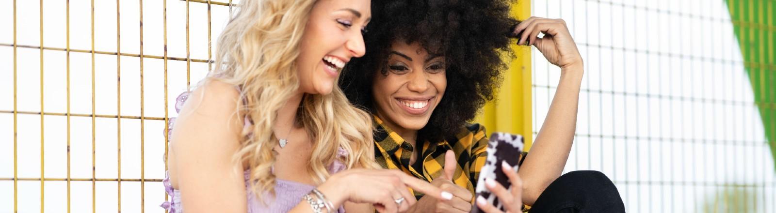 Zwei Junge Frauen lachen über etwas auf einem Handy.