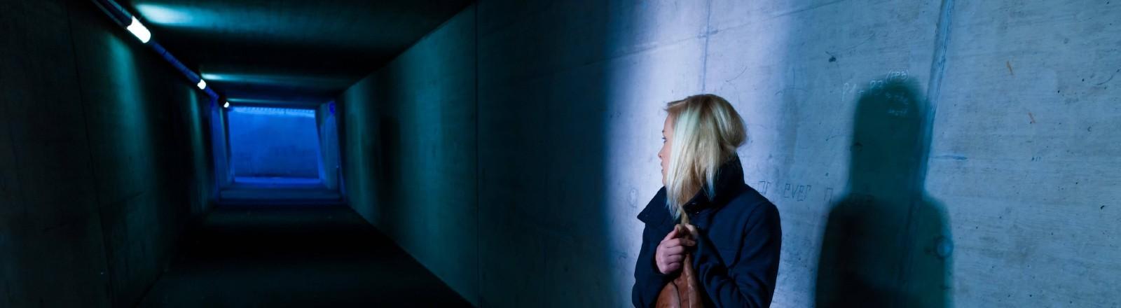 Junge Frau nachts alleine in einer dunklen Unterführung.