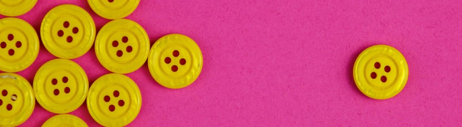 Gelbe Knöpfe auf pinkem Grund – ein Knopf liegt fernab der Gruppe abseits.