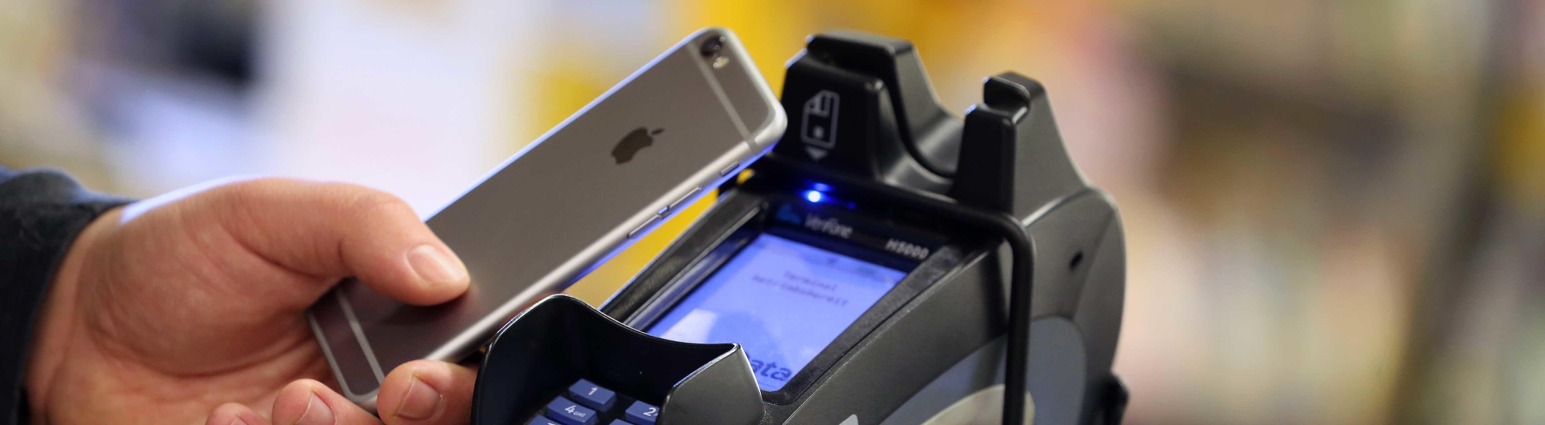 Ein iPhone wird zum Bezahlen vor ein Terminal gehalten.
