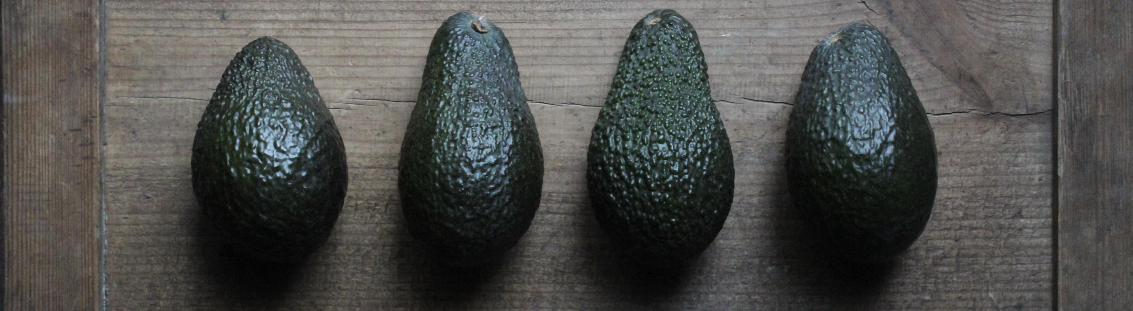 Vier Avocados liegen nebeneinander auf einem Holzbrett