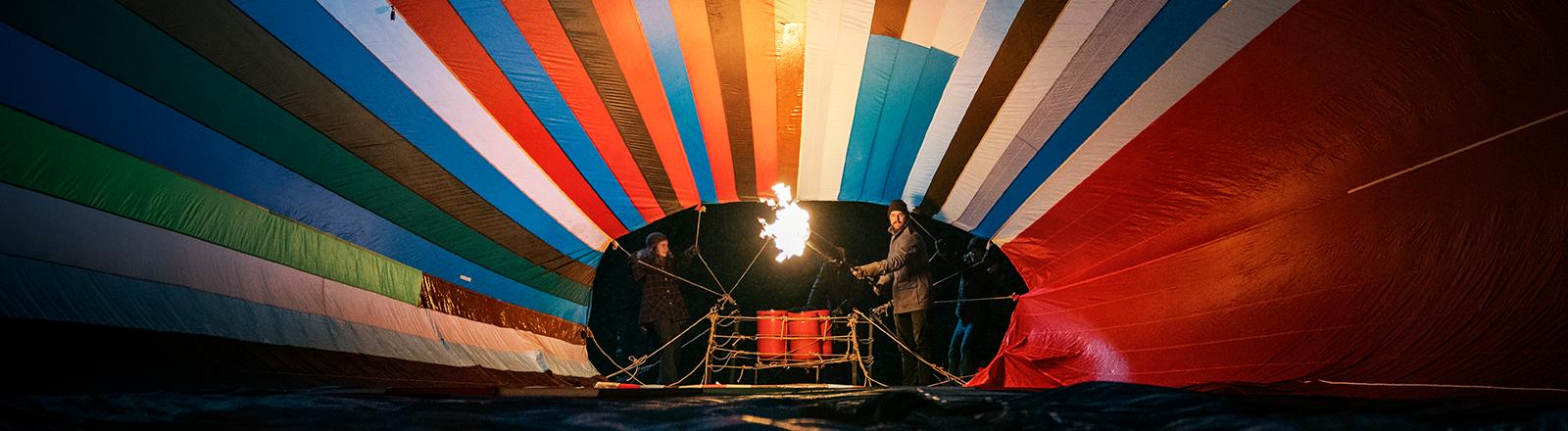 """Filmszene aus """"Ballon"""" von Bully Herbig: Kurz vor dem nächtlichen Start - Peter Strelzyk (Friedrich Mücke) heizt den Ballon ein und der entfaltet sich."""