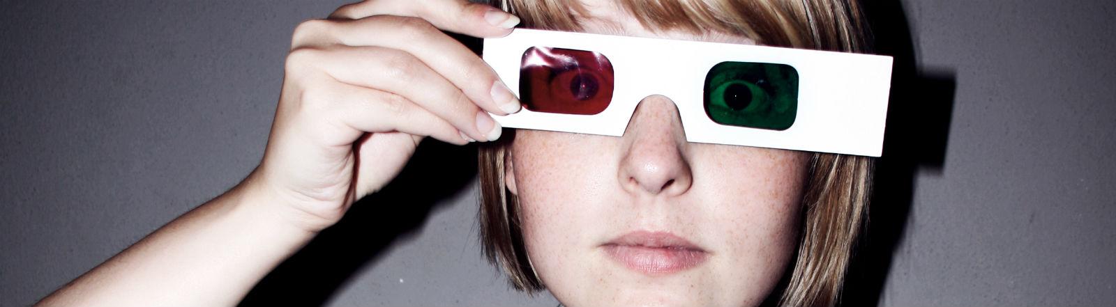 Eine Frau hält eine grün-rote Brille vor ihre Augen.