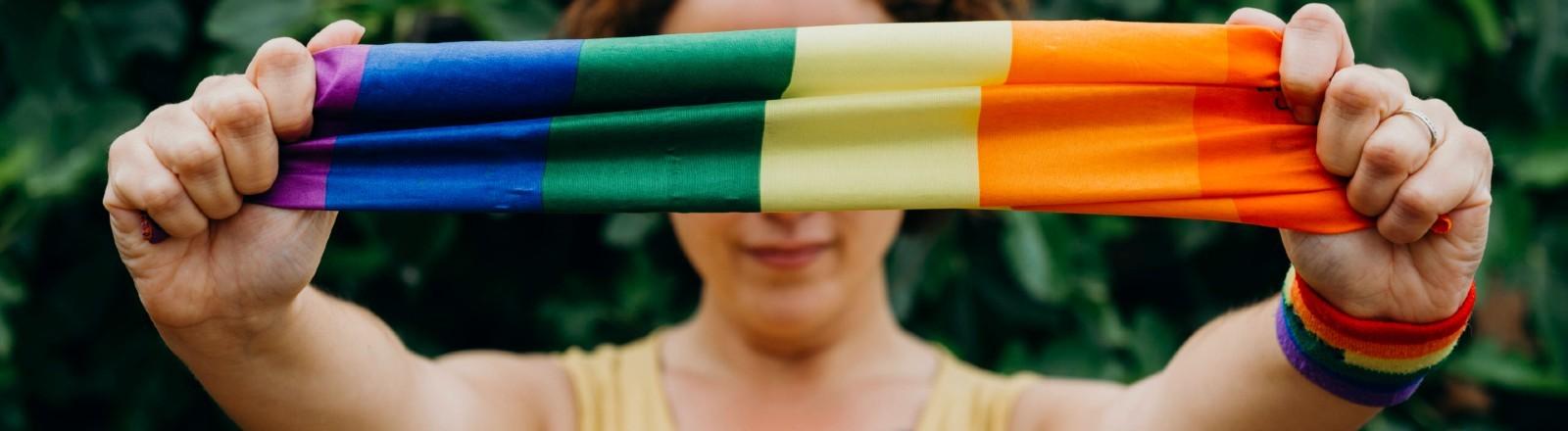 Junge Frau hält ein regenbogenfarbenes Tuch in die Kamera.