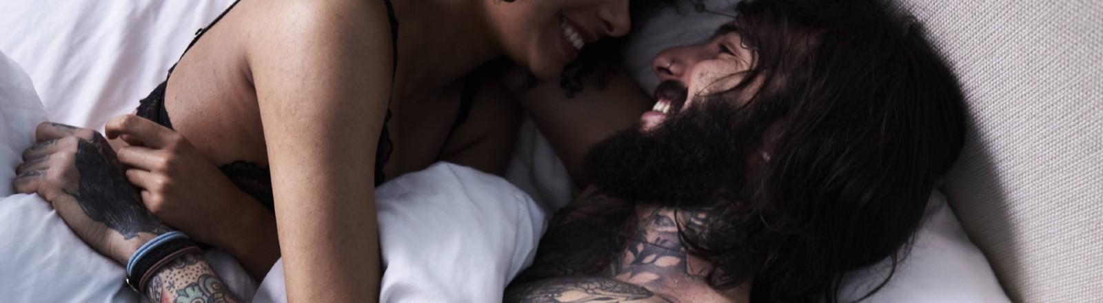 Verliebtes, junges Paar liegt im Bett.
