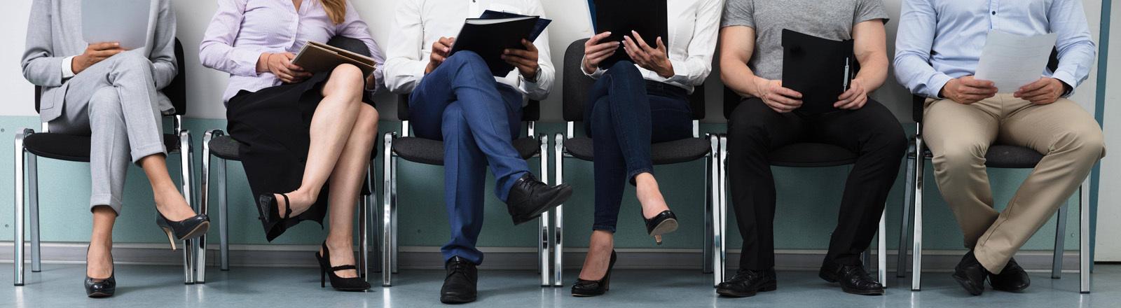 Personen sitzen mit Bewerbungsmappen auf Stühlen