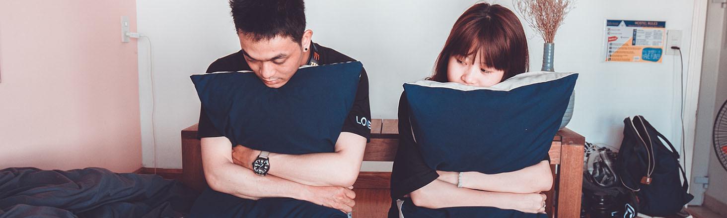 Mann und Frau sitzen nachdenklich auf Bett und umarmen Kissen