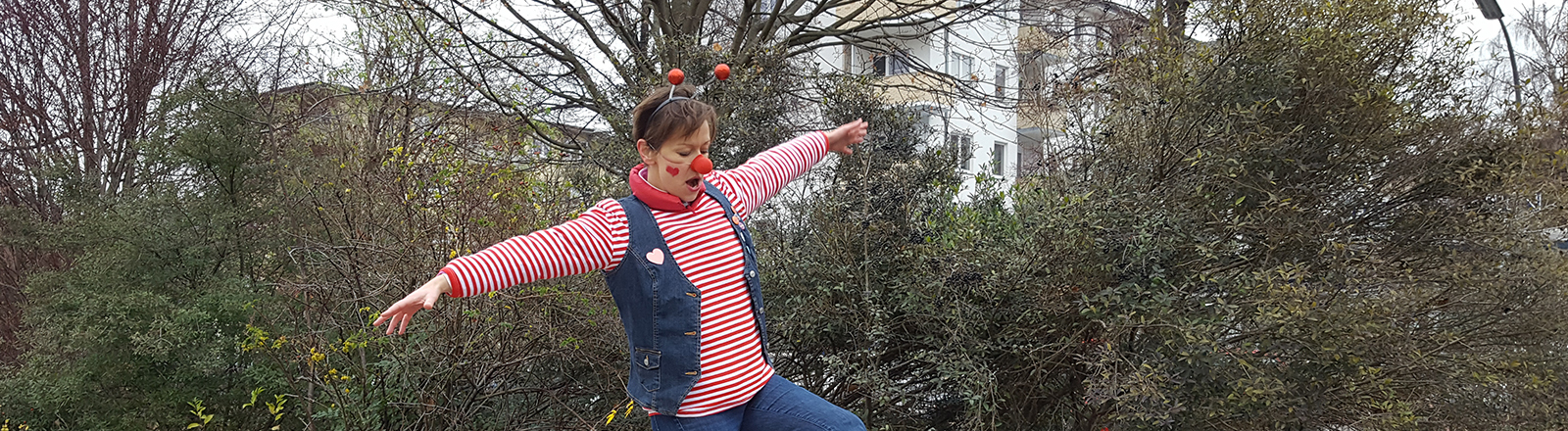 Frau im Clown-Kostüm auf roter Bank