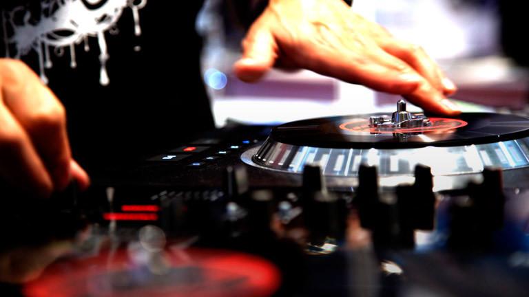 Eine Hand bedient einen Plattenteller mit Schallplatte