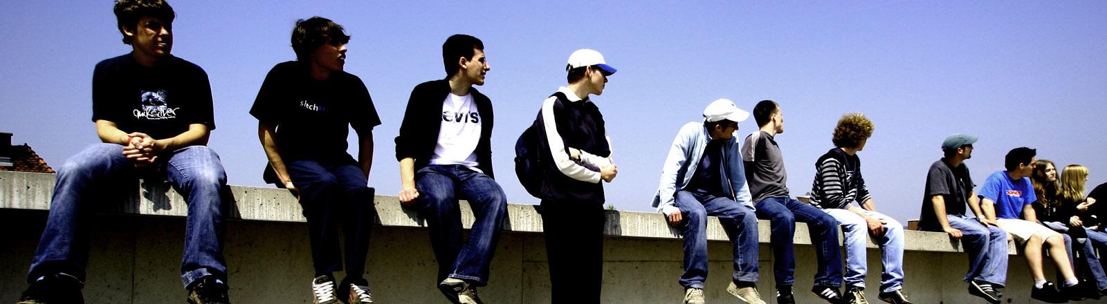 Junge Männer sitzen auf einem Hochhausdach und blicken in die Ferne.