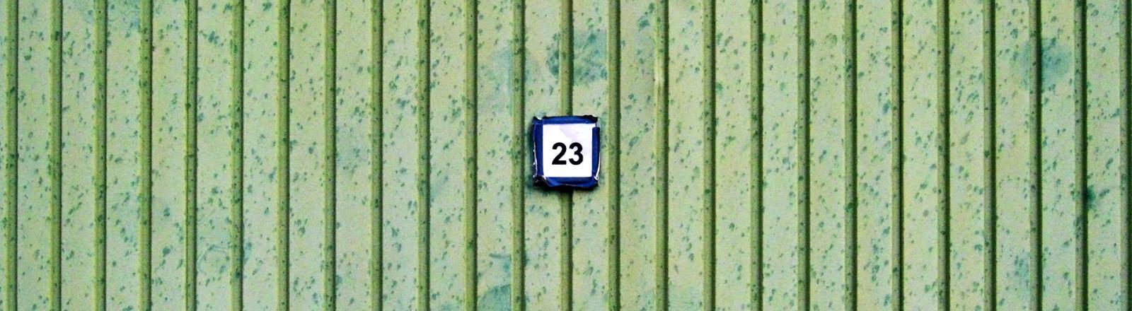 Auf einer grünen Wand hängt ein Schild, auf dem 23 steht.