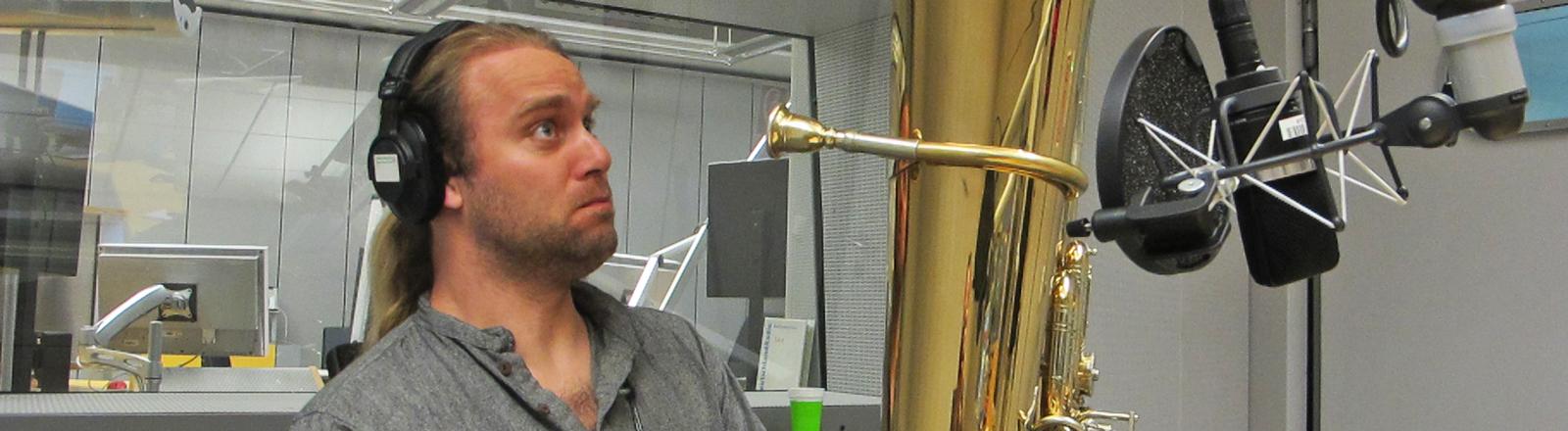 Andreas Hofmeier sitzt im Studio mit seiner Tuba vor dem Mikrofon.