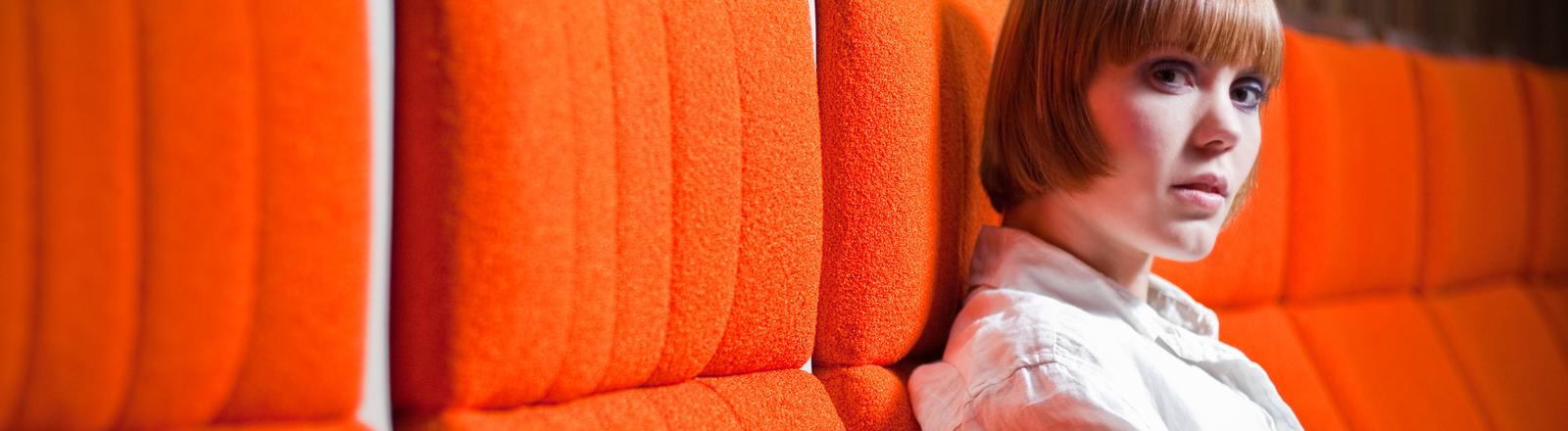 Eine junge Frau sitzt in einem Kinosessel und schaut in die Kamera.