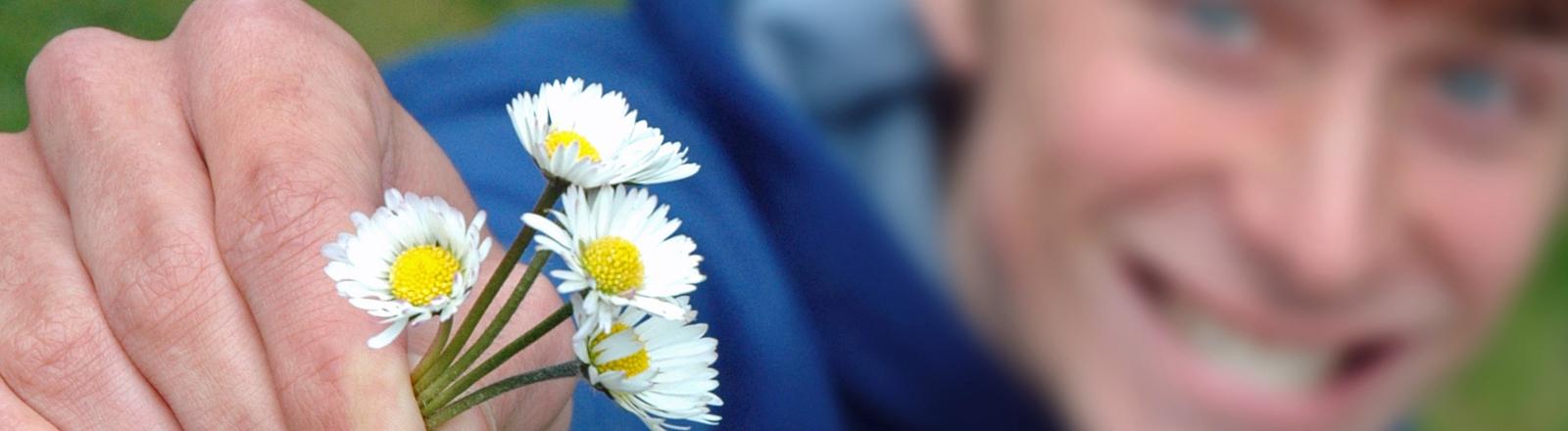 Ein Mann reicht vier kleine Gänseblümchen und grinst dabei freundlich.