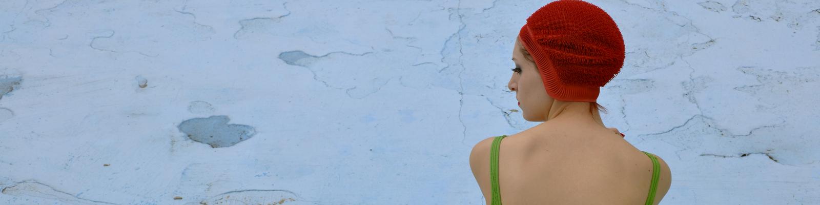 Ein Frau sitzt in Badeanzung und Bademütze neben einem großen Gummiente an einem ausgetrockneten Becken.