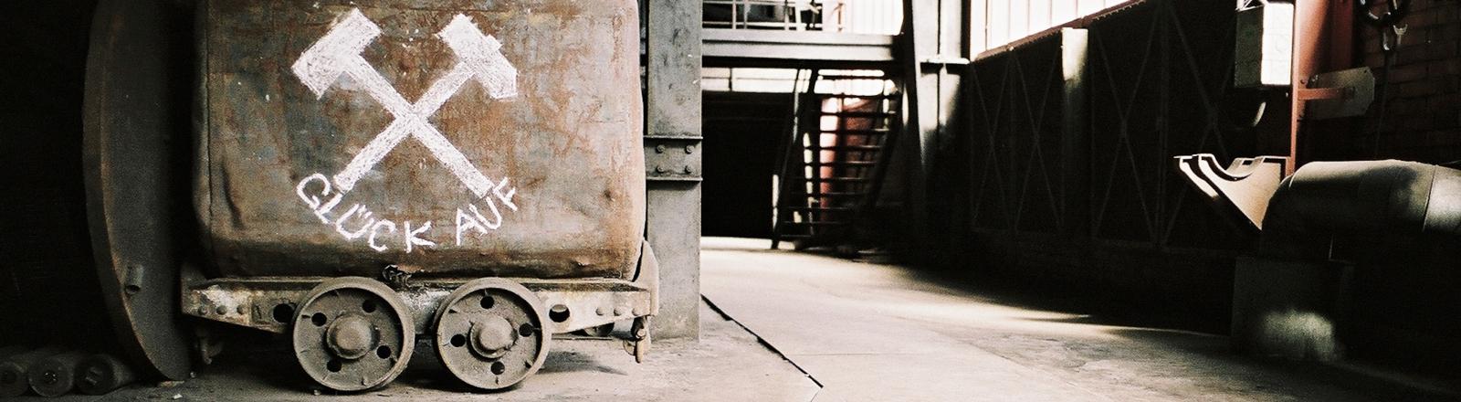 """In einer alten Industriehalle steht eine Lore, auf der """"Glück auf"""" sowie zwei Hammer, die sich überkreuzen, aufgemalt sind."""