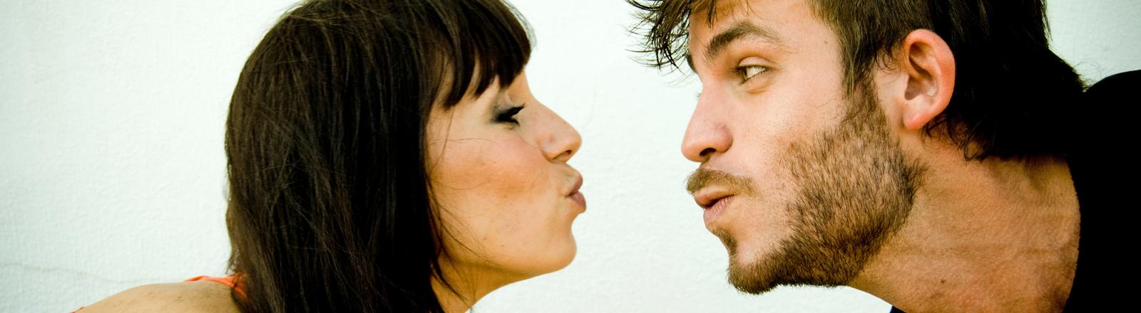 Eine Frau und ein Mann nähern sich mit gespitzten Münder einander. Sie hat die Augen verschlossen, er blickt sie an.