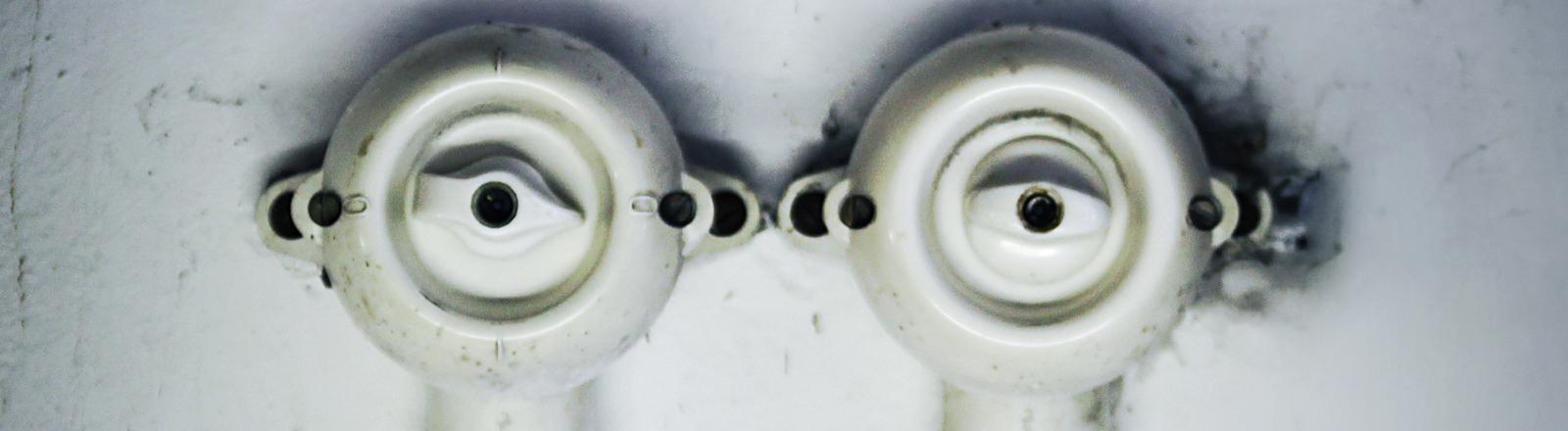 Zwei runde Lichtschalter auf einer weißen Wand direkt nebeneinander; sie ähneln einem Augenpaar.