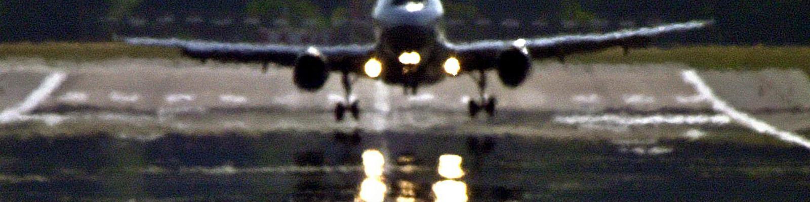Das Scheinwerferlicht eines landenden Flugzeuges auf dem Hamburger Flughafen spiegelt sich in den vor Hitze flimmernden Luftschichten über der Landebahn.