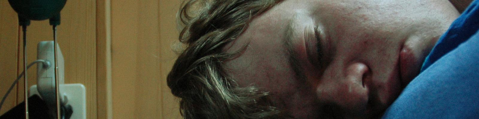 Ein junger Mann schläft komatös neben seinem Wecker.