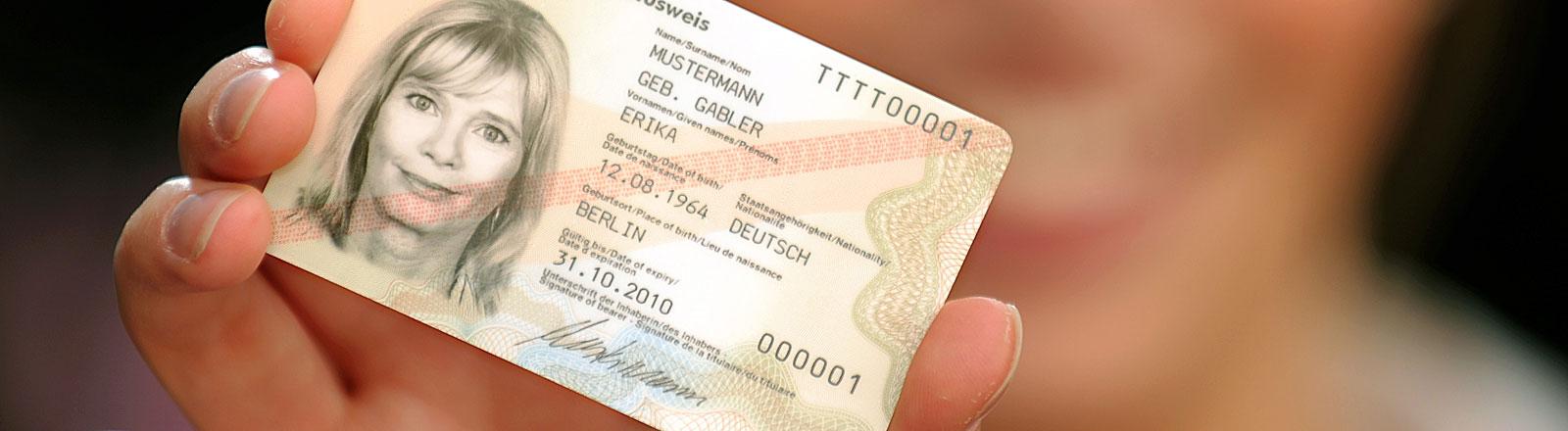 """Eine Frau hält den Personalausweis von """"Erika Mustermann"""" in die Kamera"""