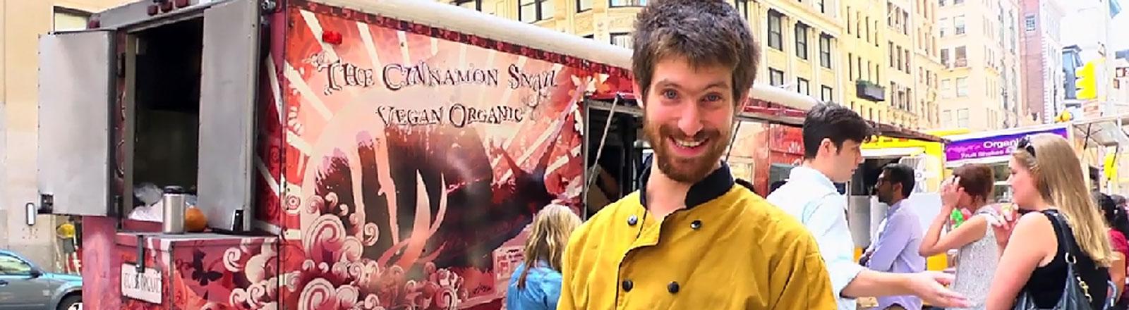 """Adam Sobel, Inhaber des Food Trucks """"Cinnamon Snail"""" vor seinem Truck."""