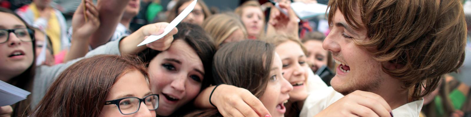 Der Youtube-Star Phil (bürgerlich Phillip Laude) der Gruppe Y-Titty umarmt am 16.08.2014 Fans am roten Teppich bei den Videodays in Köln. Bei den Videodays in der LanxessArena treffen Youtube-Fans auf ihre Stars aus dem Netz.
