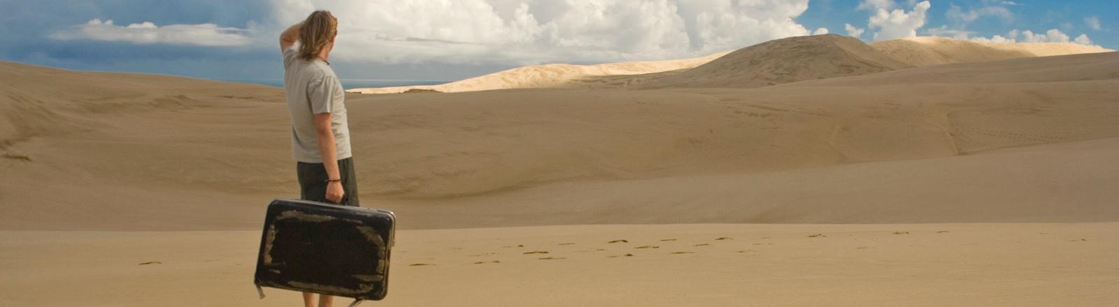 Ein Mann steht mitten in der Wüste und hält einen Koffer in der Hand. Er blickt in die Ferne.