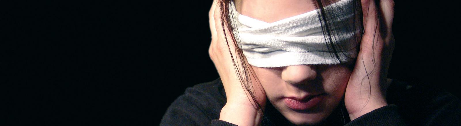 Eine Frau hält sich die Ohren zu und hat die Augen verbunden.