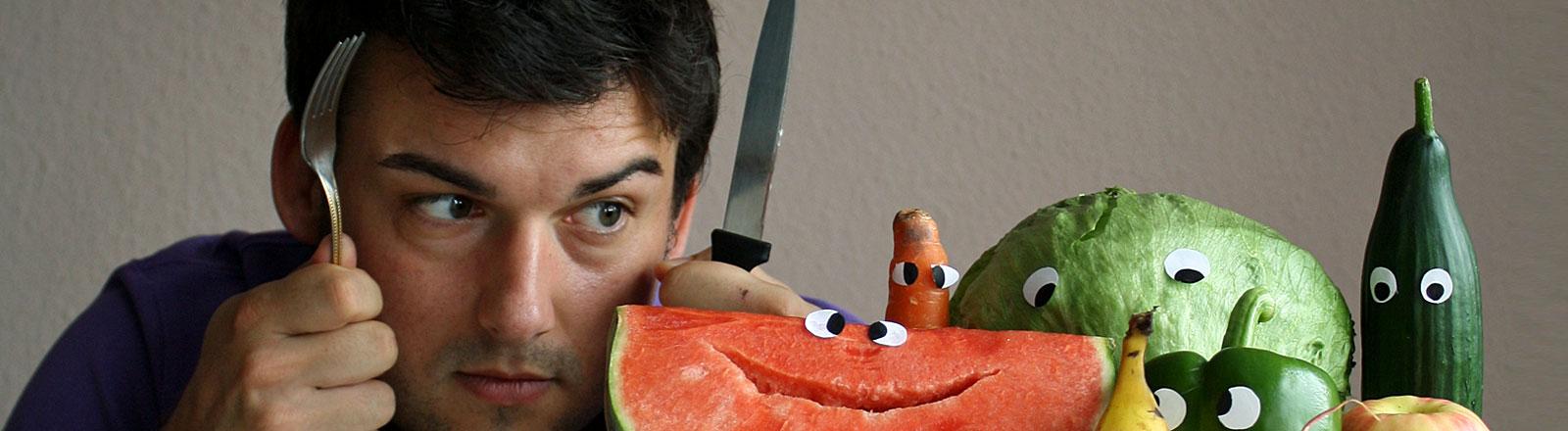 Ein Mann, Messer und Gabel gezückt, starrt auf Gemüse & Obst mit angeklebten Augen