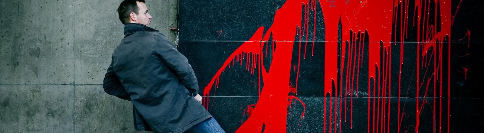 Ein Mann steht an einer Wand, als ob er pinkeln würde. Auf der Wand verläuft rote Farbe.