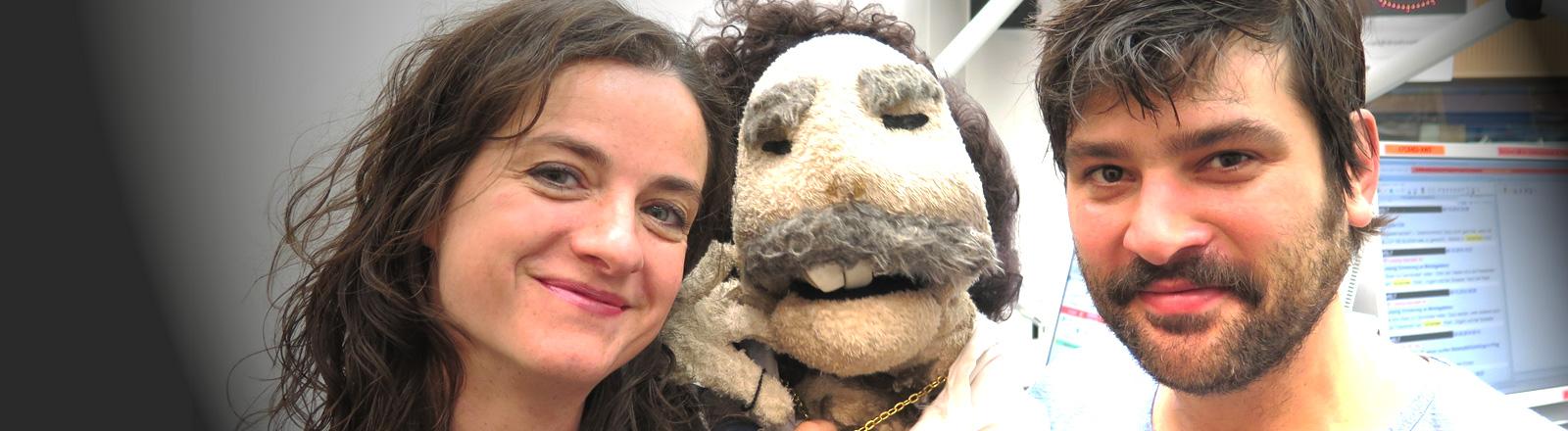 Moderatorin Daniela Tepper und Gast Jasin Challah stehen nebeneinander im Studio. Zwischen ihnen die Puppe Kosta Rapadopoulos.