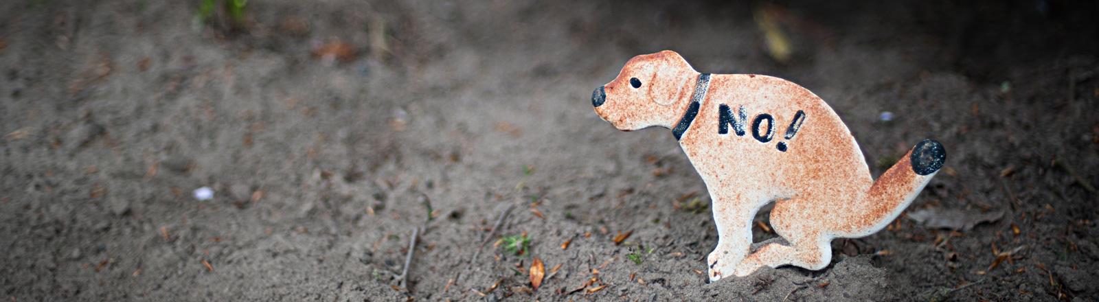 """Ein weiß-braunes Schild in Hundeform steht auf dem Boden. Der Hund ist in Kackhaltung. Auf dem Hund steht """"No!""""."""