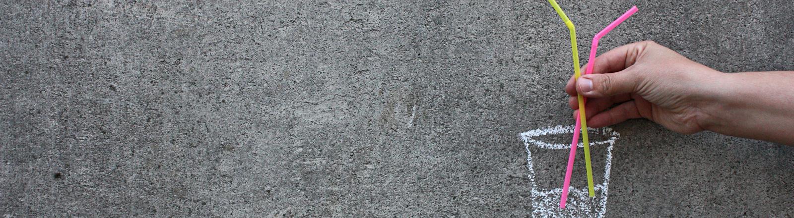 Auf eine graue Wand ist mit weißer Kreide ein Becher gezeichnet. Eine Hand hält zwei Strohhalme in den Becher.