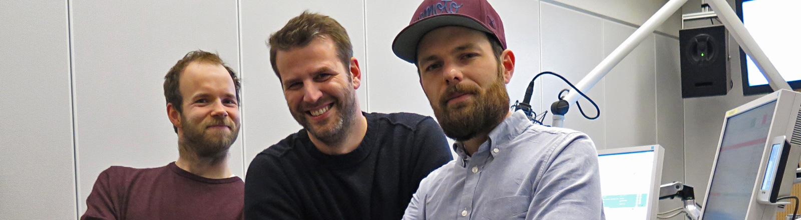 Moderator Ralph Günther steht zwischen den beiden Studiogästen Quichotte und Patrick Salmen.