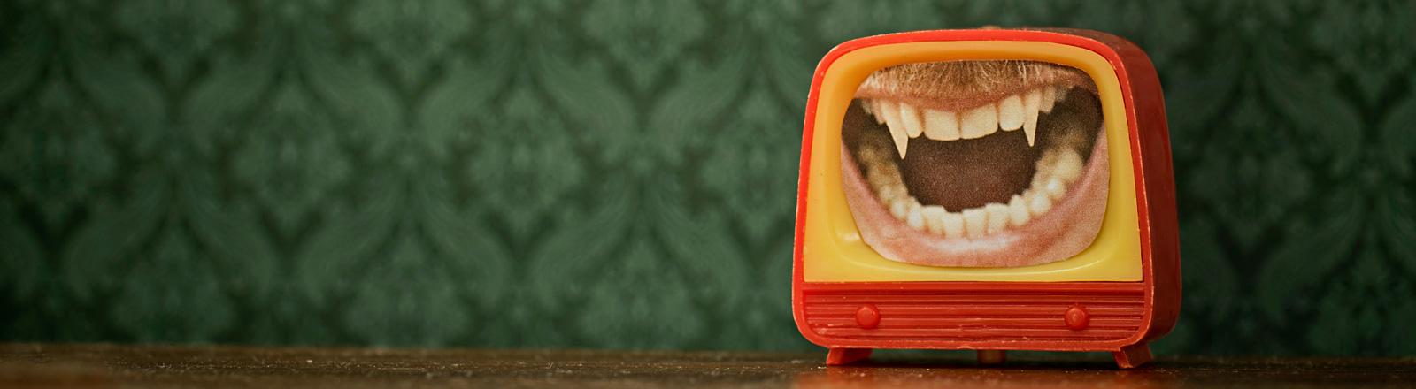 In einer kleinen Fernseher-Attrappe ist ein Foto von einem geöffneten Mund mit langen Eckzähnen, erinnert an einen Vampir. Der Fernseher steht vor einer grünen Mustertapete.