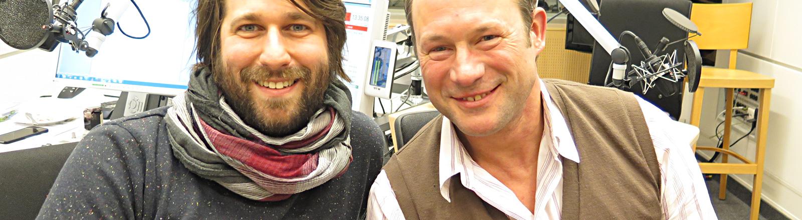 Hanno Friedrich sitzt im Studio neben Moderator Sebastian Sonntag. Sie lachen beide.